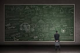 Man staring at large chalkboard with complex mathematical formulas